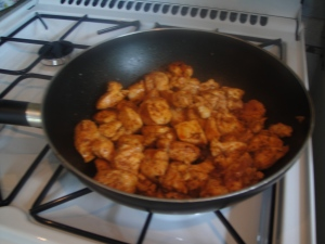 Browning the chicken in a heated wok