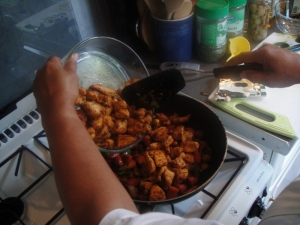Poring the browned chicken back into the wok
